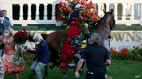 Trainer Bob Baffert is knocked to ground as Jockey John Velazquez try to control Authentic in the winners' circle after winning the 146th running of the Kentucky Derby at Churchill Downs, Sept. 5, 2020, in Louisville, Kentucky.