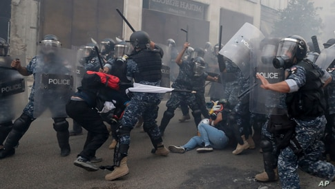 Riot policemen beat anti-government protesters during a protest near Parliament Square, in Beirut, Lebanon.