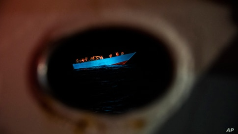 Dozens of migrants from Egypt, Morocco, Somalia and Sierra Leone, including women and minors, wait to be assisted by a team of aid workers of the Spanish NGO Open Arms, in the Central Mediterranean sea, Sept. 8, 2020.