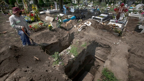 A worker digs graves in the COVID-19 section of a cemetery on the outskirts of Mexico City, Sept. 1, 2020.
