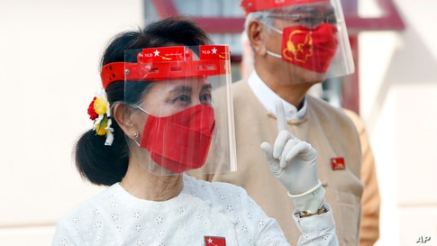 Myanmar leader Aung San Suu Kyi wearing a face shield, mask and gloves, gestures during a flag-raising ceremony to mark the first day of election campaign at the National League for Democracy party's temporary headquarters in Naypyitaw.