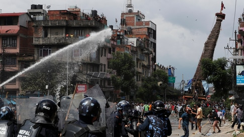 Nepalese protesters defying a government coronavirus lockdown to take part in a religious festival, clash with riot police, in Lalitpur.