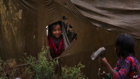 A nomadic girl talks to her sister from a ripped tent during rainfall at a slum in Peshawar, Pakistan.