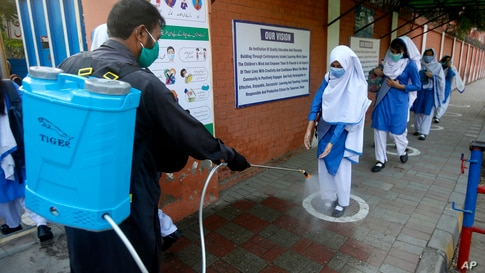 A worker disinfects shoes of a student upon her arrival at a school, in Lahore, Pakistan.