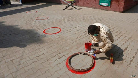 A worker paints circles for social distance at an entry gate of a school as preparation for reopening of educational institutions that were closed in March are finalized, in Lahore, Pakistan.