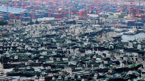 Ships are anchored at a port in Busan, South Korea.