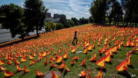 A woman walks through the flags placed in memory of coronavirus (COVID-19) victims in Madrid, Spain.