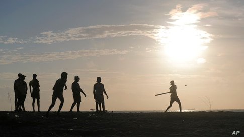 "Sri Lankan youths play a pick up game of ""Elle"", a local game similar to base ball, on the sea promenade in Colombo."