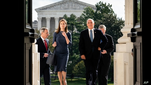 Judge Amy Coney Barrett, President Donald Trump's nominee to the Supreme Court, left, and Vice President Mike Pence arrive at the Capitol where she will meet with Senators in Washington, D.C.