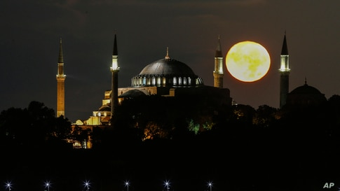 The full moon rises behind the Byzantine-era Hagia Sophia, in the historic Sultanahmet district of Istanbul, Turkey.