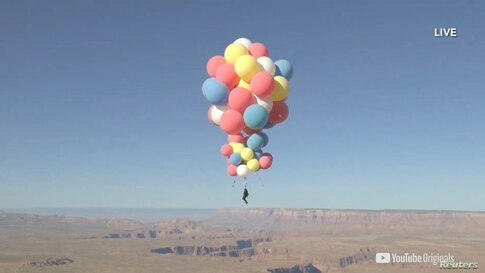 Extreme performer David Blaine hangs with a parachute under a cluster of balloons during a stunt to fly thousands of feet into the air in a still image from video taken over Page, Arizona, Sept. 2, 2020.