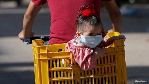A Palestinian girl wearing a protective face mask sits in a box on the back of a bicycle amid the coronavirus disease (COVID-19) crisis, in Gaza City.