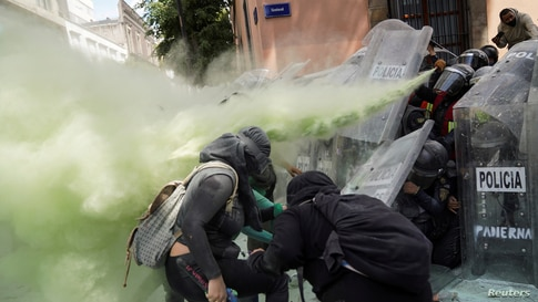 Members of a feminist collective clash with police officers during a march to mark the International Safe Abortion Day in Mexico City, Mexico, Sept. 27, 2020.