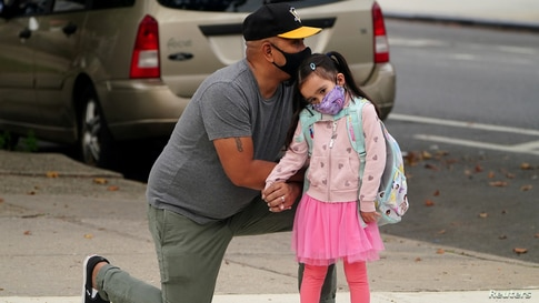 Joel Balcita comforts his daughter Sadie just before she starts her first day of grade 1 at P.S. 130 in the Brooklyn borough of New York City.