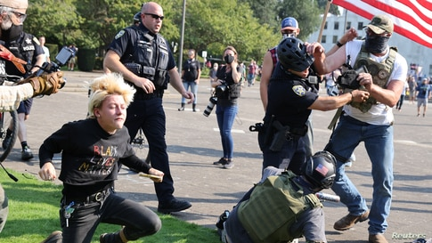 Police officers break up a fight between supporters of U.S. President Donald Trump and Black Lives Matter protesters outside the Oregon State Capitol building in Salem, Oregon, Sept. 7, 2020.