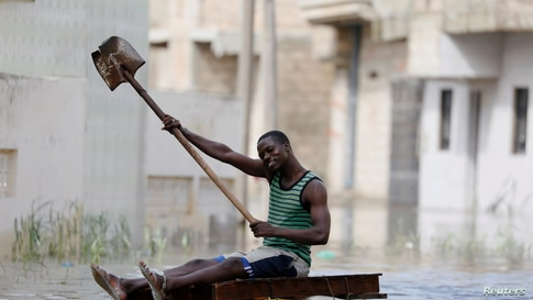 A resident uses a shovel to row through flooded streets after last week's heavy rains in Keur Massar, Senegal, Sept. 8, 2020.