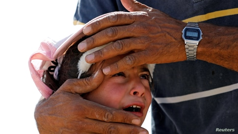 A Palestinian girl cries as she is comforted by her uncle after Israeli forces demolished her family's house near Hebron in West Bank.