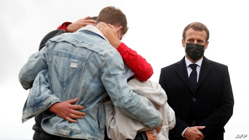French President Emmanuel Macron (R) stands next to French aid worker Sophie Petronin (C) who is welcomed by her family after…