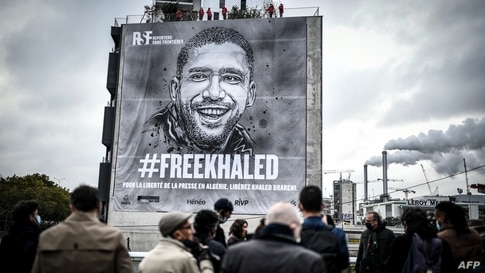People attend the installation of a tarp depecting jailed Algerian journalist Khaled Drareni by French street artist and…
