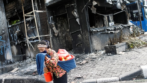 A traditional drink vendor reacts as she passes a burned police station a day after a protest against the government's…
