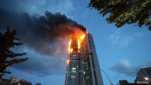 A mixed-use high-rise residential building is engulfed by a fire in Ulsan, South Korea, October 9, 2020.    Yonhap via REUTERS …