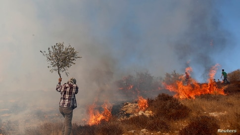 A Palestinian demonstrator tries to put out a fire caused by tear gas canisters fired by Israeli troops  during a protest…
