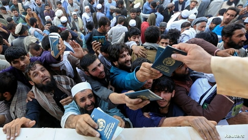 Afghan men wait to collect tokens needed to apply for the Pakistan visa, in Jalalabad, Afghanistan October 21, 2020. REUTERS…