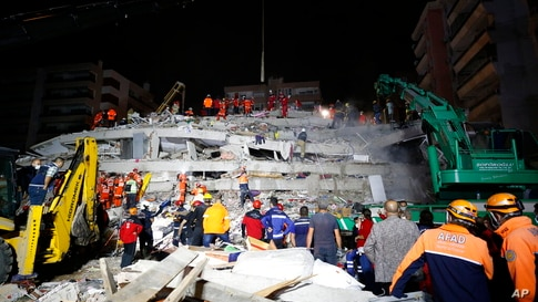 Members of rescue services search in the debris of a collapsed building for survivors in Izmir, Turkey, early Saturday, Oct. 31…