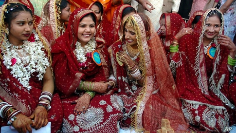 FILE - Brides from Hindu and Muslim community Dharmishtha, left, Feminabanu, second left, Bina, second right, and Rehanabanu, right, share a light moment during an all religious mass marriage at Dariapur police station in Ahmadabad, India.