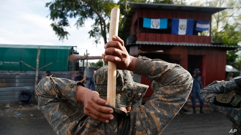 A soldier places a handmade, wooden stick into the back of his uniform as he stands guard in El Cinchado, Guatemala, on the border with Honduras. Guatemala vowed to detain and return members of a caravan of about 2,000 migrants hoping to reach the U.S.