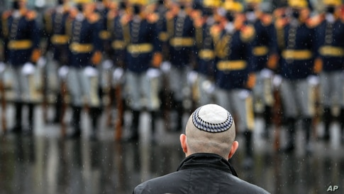 Silviu Vexler, a member of parliament representing the Jewish community speaks, backdropped by members of an honor guard,…