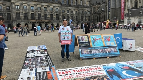 Abdurehim Gheni stands in demonstration with pictures of his relatives and other disappeared Uighurs, at Dam Square in Amsterdam in July. (Photo courtesy: Abdurehim Gheni)