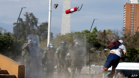 Demonstrators clash with riot police during a protest at Plaza Italia square in Santiago against the Chilean police, Oct. 03, 2020, after Antony Araya, 16, fell from a bridge while police was attempting to arrest him during Friday clashes.