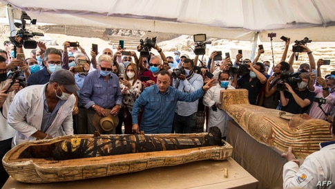 Egyptian Minister of Tourism and Antiquities Khaled Al-Anani (L), and Mustafa Waziri (R), Secretary General of the Supreme Council of Antiquities unveil the mummy inside a sarcophagus excavated at the Saqqara necropolis, south of the capital Cairo.