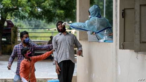 Residents hold a man as a health worker collects a swab sample from him to test for the Covid-19 at a community gym on the outskirts of Hyderabad, India.