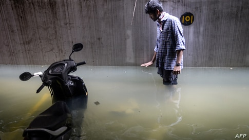 A resident shows the level of water in his cellar area at an apartment following heavy rains in Hyderabad, India.