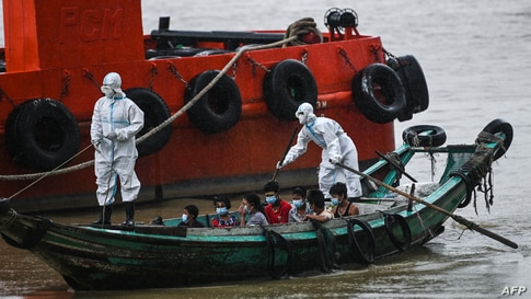 Volunteers wearing personal protective equipment (PPE) on a boat transfer people suspected of having the coronavirus to a quarantine center in Yangon, Myanmar.