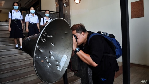 A man takes a photo of a loudspeaker ridden with bullet holes during the Thammasat University massacre on October 6, 1976, at an exhibition commemorating the event at Thammasat University in Bangkok, Thailand.
