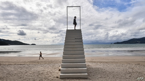 A girl stands on a set of stairs on Patong beach in Phuket, Thailand.