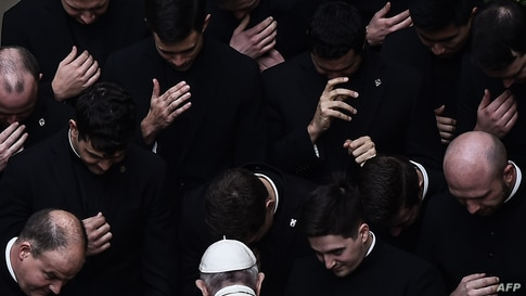 Pope Francis prays with priests at the end of a limited public audience at the San Damaso courtyard at the Vatican, Sept. 30, 2020.