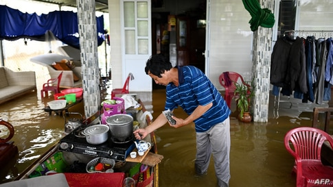Phan Gia Quang makes tea at his flooded house in Quang Dien district in central Vietnam's Hue province.