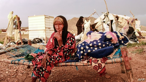 An elderly woman sits on a make-shift bed as people try to salvage tents damaged by torrential rain, at a camp for Yemenis displaced by conflict in the northern Hajjah province, Sept. 30, 2020.