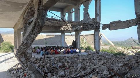 Students attend class on the first day of the new academic year, in a makeshift classroom in their school compound which was heavily damaged two years ago in an airstrike, in Yemen's third-city of Taez.
