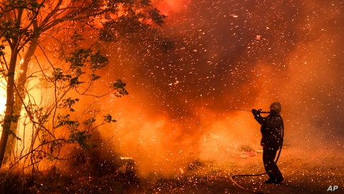 A firefighter battles flames in Cordoba, Argentina, Oct. 12, 2020. Wildfires have destroyed thousands of hectares in the Argentine province of Cordoba this year, amid a drought and high temperatures.