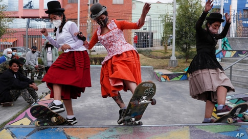 """Milenda Limachi, left, Yanira Villarreal, center, and Ayde Choque, dressed as a """"Cholitas"""" ride their skateboards during a youth talent show in La Paz, Bolivia, Sept. 30, 2020"""