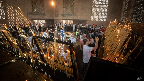 People light candles inside Our Lady of Aparecida Basilica, the temple of Brazil's patron saint, in Aparecida.