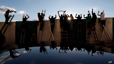Fans, standing on ladders behind the fence, celebrate a goal as they watch a Czech first division match between Bohemians Prague and Zlin in Prague, Czech Republic, Oct. 4, 2020.