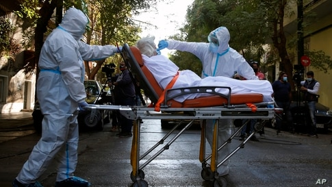 A paramedic with a special suit to protect against coronavirus, adjusts the face mask of a patient as his colleague pulls the stretcher out of a nursing home where dozens of elderly people have been found positive to COVID-19, in Athens, Greece.