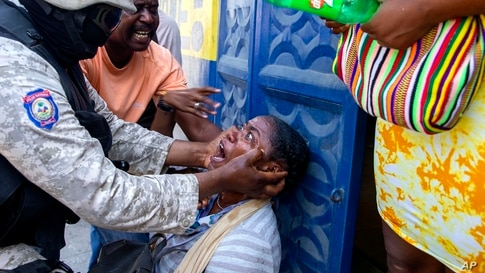 A bystander is assisted by police after officers fired tear gas to disperse a protest in Port-au-Prince, Haiti, Oct. 5, 2020.…