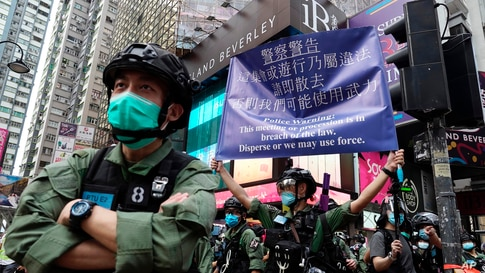 A police officer displays a warning banner on China's National Day in Causeway Bay, Hong Kong.